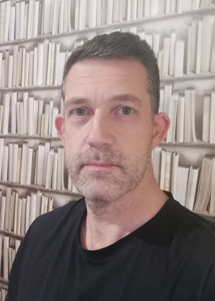 Photo of illustrator Chris Mould in front of books
